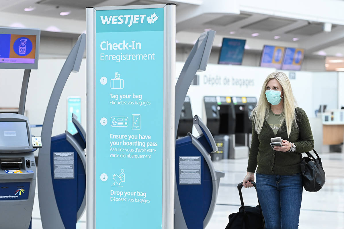 A woman walks through check in at WestJet at Pearson International airport during the COVID-19 pandemic in Toronto on Wednesday, Oct. 14, 2020. THE CANADIAN PRESS/Nathan Denette